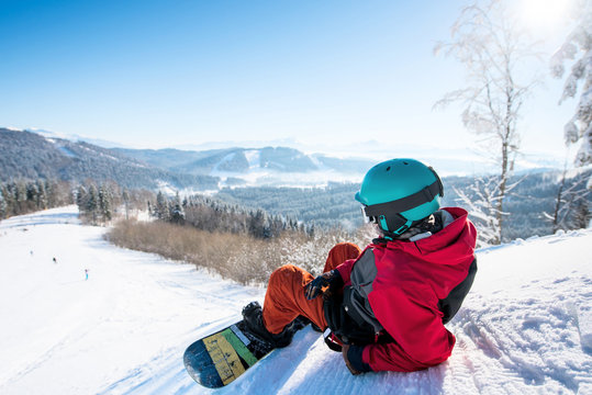 Rearview shot of a relaxed man snowboarder lying on the snowy slope enjoying stunning mountains view resting after riding at the winter resort copyspace landscape recreational lifestyle activity