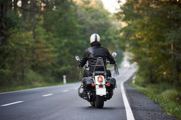 Back view of biker in black leather jacket and white helmet riding motorbike along hilly road between tall green trees. Active lifestyle, love to adventures concept. Wall mural