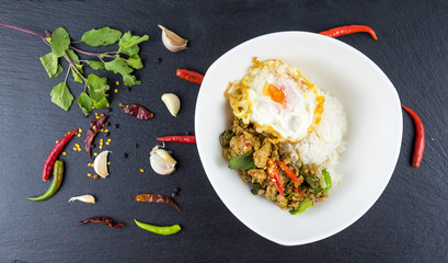 Spicy Thai basil with Crispy Chicken and Egg (Pad Krapow Gai) on table . it is a very delicious Thai food. Rice topped with stir-fried pork and basil leaves . street food in Thailand.