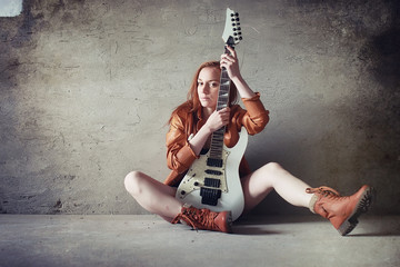Young red-haired girl with an electric guitar. Rock musician girl in a leather jacket. She is a pretty singer and a performer of rock music.