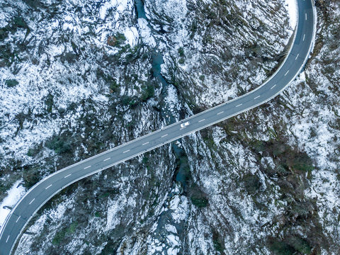 Aerial view of road bridge in Switzerland over a deep valley in winter with snow covered ground. Icy conditions.