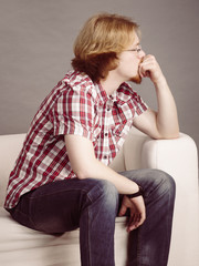 Young man thinking and sitting