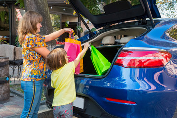 A mother with a little daughter are putting their luggage in a car trunk.
