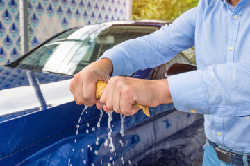 A man's hands are twisting a wet cloth at the car background.