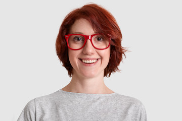 Close up shot of smiling glad woman with short hairstyle, wears red rimed spectacles, dressed casually, isolated over white background, expresses positive feelings. People and beauty concept.