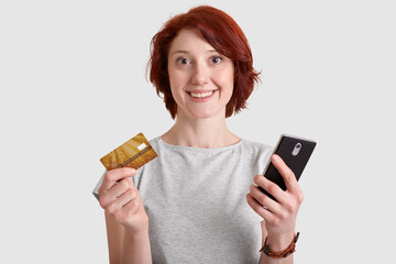 Horizotnal shot of pleased woman with gentle smile, foxy hair, holds mobile phone and credit card, makes money transactions, transfers money, enjoys online shopping, checks her bank account.