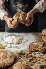 Man breaking off piece of rustic rye bread, standing at table with dough in flour, closeup