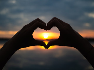 Silhouette hands to be heart shape on sunset background. Happy, Love, Valentine's day idea, sign, symbol, concept.