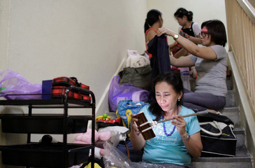 Filipina domestic worker Ruth Tolentino Funtecha uses her mobile phone during a giveaway of donated and dumpster dived items outside the house of Singaporean freegan Sarah Ng in Singapore