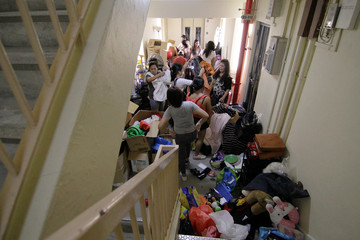Filipina domestic workers look through boxes during a giveaway of donated and dumpster dived items outside the house of Singaporean freegan Sarah Ng in Singapore