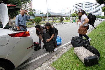 Filipina domestic workers Lora Bravo, Virginia Andrade, and Gina Delos Santos load a taxi with bags of items they got for free, after a giveaway of donated and dumpster dived items at the house of Singaporean freegan Sarah Ng, in Singapore