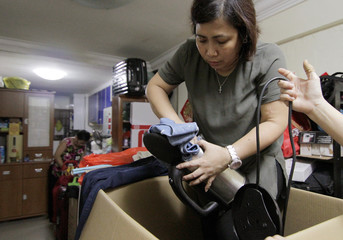 Filipina administrator Myrna Cabrera puts clothes into a water kettle as she packs a box with donated and dumpster dived items at the house of freegan Cynthia Yap in Singapore