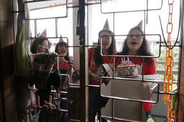 """Filipina domestic workers sing """"Happy Birthday"""" as they arrive for a giveaway of donated and dumpster dived items at the house of Singaporean freegan Colin Lau, a day after his birthday, in Singapore"""