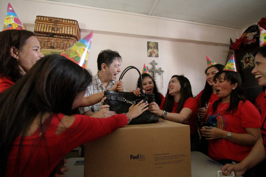 Filipina domestic workers react as Singaporean freegan Colin Lau reveals a Coach handbag during a free giveaway of donated and dumpster dived items at his house in Singapore