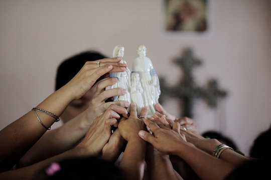 Filipina domestic workers reach out to touch a religious figurine held up by Singaporean freegan Colin Lau, as they pray during a free giveaway of donated and dumpster dived items at his house in Singapore