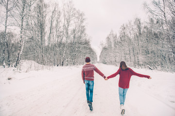 Teenagers in Christmas sweaters walking in snow in winter