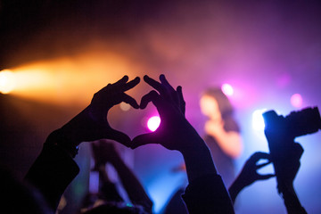 Concert in the club, the hands of the people in front of those lights. sign of the heart,