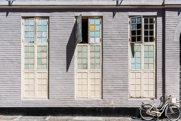 Painted wooden wall with windows and a bicycle of a historic building in the center of Copenhagen, Denmark.
