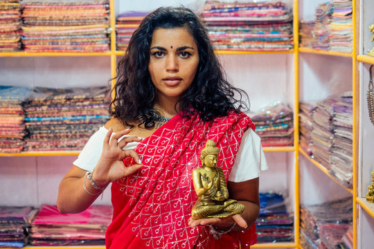 business lady indian seller tradition red sari souvenir shop buddha shiva figurine yoga meditation.girl in india in the religion store.beautiful woman with bijouterie jewelry earrings Delhi Bazaar