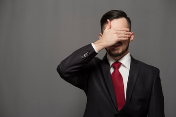 Close-up - serious businessman or manager closes his eyes by hand. Copyspace