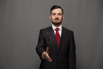 You are our client. Businessman wearing formal suit and glasses holds out his hand for a handshake on gray background