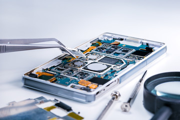 Repairing the smartphone's motherboard in the lab. the concept of computer hardware, mobile phone, electronic, repairing, upgrade and technology.