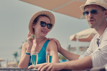 Young European couple is sitting at the pool bar and enjoying their vacations. They are celebrating something and drinking champagne.