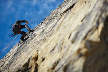 Foto op Aluminium Alpinisme The climber is hanging on a safety rope on a rock wall.