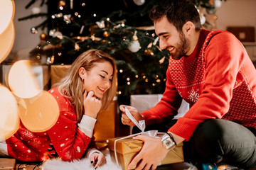 Happy couple enjoying Christmas morning and opening gifts wearing matching sweaters