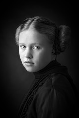 Beautiful classic young girl with alabaster skin and iconic braided ear buns wearing a pleated shirt and silk scarf.