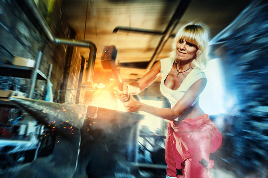 Woman blacksmith forges metal on the anvil with the sledgehammer. Workshop on the background.