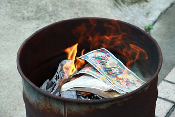 Burning the silver and gold fake money paper for chineses dead people  ancestors. Joss paper money burning metal bugket dead  in chinese new year.