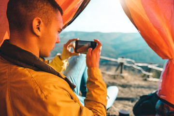 Young male hiker taking a picture of nature inside of a tent in Serbia