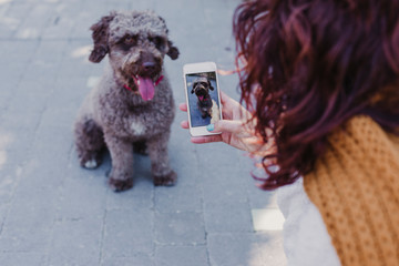 young woman taking a selfie to her dog. outdoors
