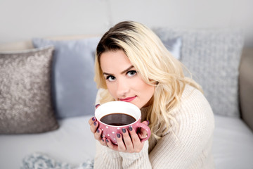 Young woman sitting in bed with cup of coffee