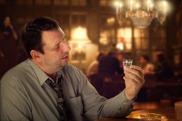Man in depression sits lonely at the pub