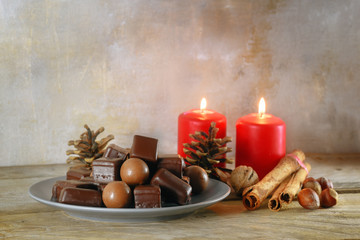 chocolate balls and gingerbread cookies, in germany called dominosteine, red candles and decoration for Advent and Christmas on a rustic wooden table, copy space