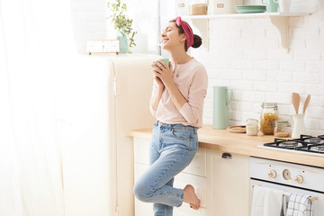 Young woman drinking a morning coffee in kitchen  Wall mural