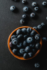 blueberries in a wooden bowl on a black slate background
