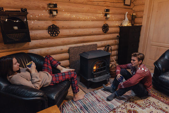 Friends relaxing by the fireplace in log cabin