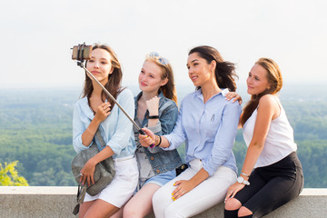 Beautiful funny girlfriends make selfies in the mountains on the background of nature. travel, summer, weekend, walk
