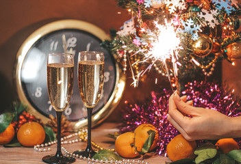 Christmas composition consisting of hours, the arrow of which is at 12 o'clock, glasses of champagne with bubbles, sparklers in the hand of a girl, decorated Christmas tree, tangerines and other