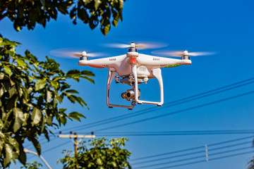 drone with camera flying with trees, pole, electricity wires and blue sky in the background