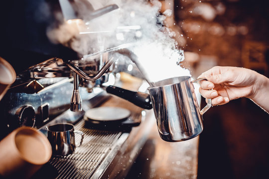 Barista whips milk with nozzle, strong jet of air steam coffee machine, holding pitcher in his hand