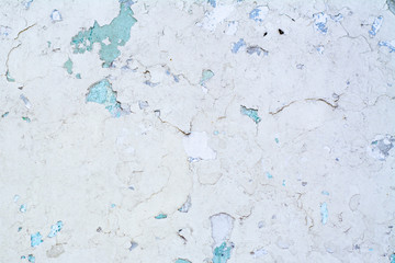 White painted concrete wall with peeling paint and blue stains in the cracks