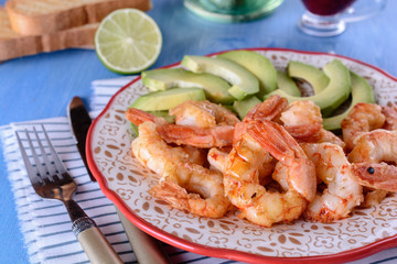 Grilled shrimps next to fresh avocado slices on a plate next to lime, knife and fork on a blue wooden background