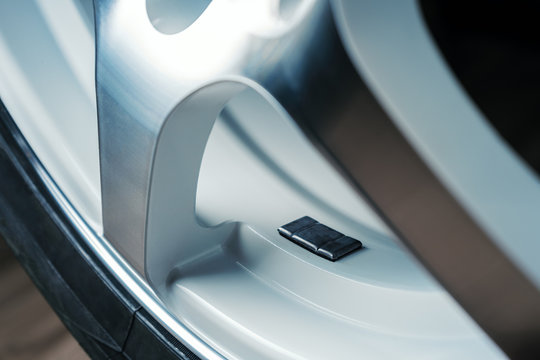 A fragment of the wheel of a car with a balancing weight