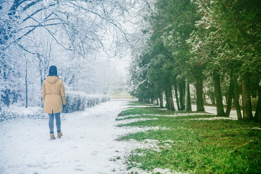 woman walk by park where winter meet spring