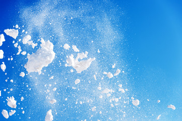 throwing snow into the air on a blue background