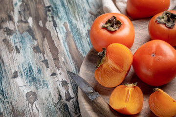 Fresh persimmon fruits on board and knife with copy space